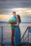 Красивые пары в влюбленности на старом мосте на предпосылке неба захода солнца Стоковые Фото