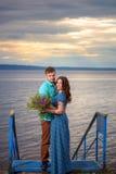 Красивые пары в влюбленности на старом мосте на предпосылке неба захода солнца Стоковое Изображение RF