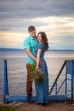 Красивые пары в влюбленности на старом мосте на предпосылке неба захода солнца Стоковое Изображение