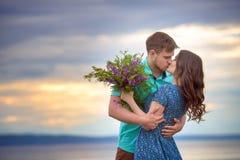 Красивые пары в влюбленности на старом мосте на предпосылке неба захода солнца Стоковые Изображения RF