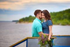 Красивые пары в влюбленности на старом мосте на предпосылке неба захода солнца Стоковое Фото