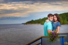 Красивые пары в влюбленности на старом мосте на предпосылке неба захода солнца Стоковые Фотографии RF
