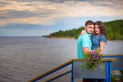 Красивые пары в влюбленности на старом мосте на предпосылке неба захода солнца Стоковая Фотография RF