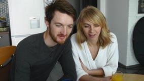 Красивые пары в влюбленности наслаждаются утром в квартире Молодая семья выпивая апельсиновый сок на даме завтрака привлекательно сток-видео