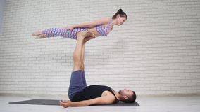 Красивые пары делая йогу acro в студии видеоматериал