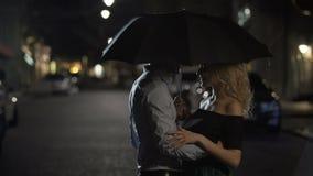 Красивые пары любовников обнимая под зонтиком, датой ночи, любовной историей видеоматериал