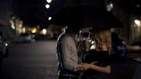 Красивые пары любовников обнимая под зонтиком, датой ночи, любовной историей стоковые изображения rf
