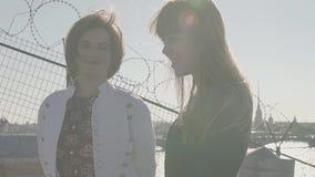 Красивые пары маленьких девочек на крыше с сценарным взглядом реки города сток-видео