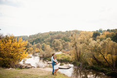 Красивые пары обнимая один другого около реки горы Стоковые Изображения
