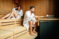 Красивые пары ослабляя в сауне Стоковая Фотография