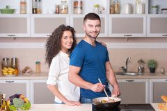 Красивые пары подготавливая ужин совместно внутри стоковая фотография