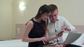 Красивые пары сидя на кровати и используя smartphone, смотря счастливый совместно акции видеоматериалы