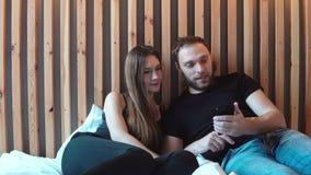 Красивые пары сидя на кровати и смотря фото от отключения на smartphone, касающем экране Смех человека и женщины видеоматериал