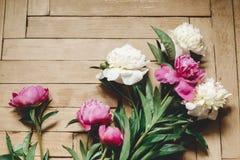 Красивые пионы пинка и белых на деревенском деревянном поле, плоском положении Флористическое оформление и расположение : Сельски стоковое фото rf