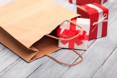 Красивые подарочные коробки с красным и белым смычком на деревянной предпосылке Стоковая Фотография