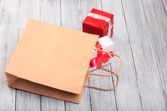 Красивые подарочные коробки с красным и белым смычком на деревянной предпосылке Стоковые Изображения RF
