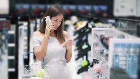 Красивые покупки девушки в косметическом магазине и ответах телефонном звонке, замедленном движении сток-видео