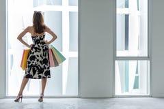 Красивые покупки женщины настолько счастливые онлайн с ее покупками в случайной одежде с хозяйственными сумками, стойке около буш стоковое изображение rf