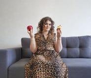 Красивые полные яблоко вьющиеся волосы девушки и торт, софа эмоции выражения отборная Стоковые Фото
