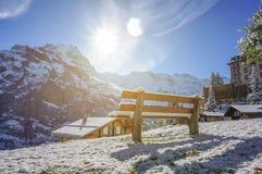 Красивые посадочные места деревянной скамьи в блеске da солнца горной вершины горы снега Стоковая Фотография RF