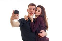 Красивые поцелуи девушки на щеке молодых привлекательных парня и его делают selfi на телефоне Стоковые Изображения RF