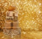 Красивые подарочные коробки в бумаге золота с шелком подняли стоковое изображение rf