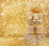 Красивые подарочные коробки в бумаге золота с шелком подняли стоковое фото