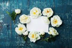 Красивые розовые цветки, листья зеленого цвета и чистый бумажный лист на голубом винтажном взгляде столешницы в стиле положения к Стоковое Фото