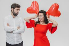 Красивые романтичные пары изолированные на белой предпосылке Привлекательная молодая женщина держит воздушные шары над ее головой стоковое фото rf