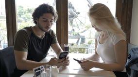 Красивые романтичные пары сидя в ресторане использующ и смотрящ smartphone видеоматериал