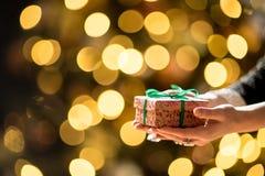 Красивые руки женщины держа подарок рождества, абстрактную золотую предпосылку света bokeh стоковая фотография rf