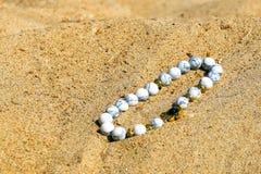Красивые самоцветные каменные шарики на песке моря стоковое изображение