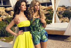 Красивые сексуальные девушки в платьях представляя на пляже Стоковое Фото