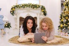 Красивые сестры смеются над и с помощью PA карточки устройства и банка Стоковые Фото