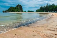 Красивые скалы покрытые с деревьями на песочном береге Стоковые Изображения