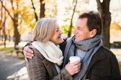 Красивые старшие пары обнимая в парке, выпивая кофе Осень Стоковые Изображения RF