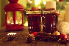 Красивые 2 стекла обдумыванных вина или чая на коричневой деревенской деревянной таблице предпосылки против подарков рождества с  стоковые изображения rf
