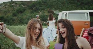 Красивые стильные дамы на пикнике выпивая что-то от стекел и принимая selfies от телефона, предпосылки акции видеоматериалы