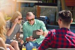 Красивые стильные друзья используют цифровую таблетку, выпивая кофе и усмехаются пока отдыхающ в парке Стоковое Изображение RF