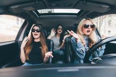 Красивые стильные девушки сидят с открытым ртом пока имеющ удар во время вождения автомобиля Стоковые Фото