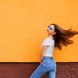 Красивые стильные женщины Волосы летания Померанцовая предпосылка Экземпляр-космос стоковая фотография
