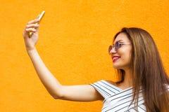 Красивые стильные женщины делая selfie Померанцовая предпосылка Экземпляр-космос стоковые изображения