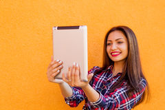 Красивые стильные усмехаясь женщины делают selfie таблеткой Померанцовая предпосылка Экземпляр-космос стоковое изображение