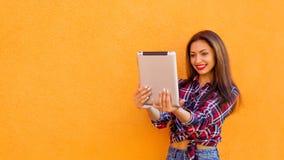 Красивые стильные усмехаясь женщины делают selfie таблеткой Померанцовая предпосылка Экземпляр-космос стоковые фото