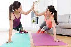 Красивые счастливые девушки делая спорт фитнеса дома Стоковое Фото