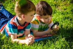 Красивые счастливые дети, братья мальчика, исследуя природа с лупой, летнее время стоковое фото rf