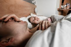 Красивые счастливые молодые пары или семья просыпая вверх совместно в кровати стоковая фотография rf