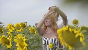 Красивые счастливые танцы пар совместно на поле солнцецвета Девушка имбиря с ее парнем отдыхая outdoors сток-видео