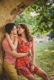 Красивые счастливые любящие пары на природе близко к большому дереву обнимая и смотря один другого За момент до поцелуя Стоковые Изображения