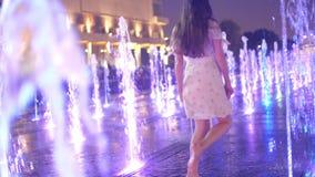 Красивые танцы в загоренном фонтане в вечере, замедленное движение молодой женщины видеоматериал